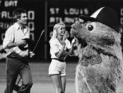 Ted Turner helps out base sweeper during the 5th inning, along with the Braves monster. (Undated, probably late 1970s)